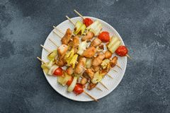 Kebab chicken, zucchini and tomatoes on skewers in a plate. Dark table Copy space. Kebab chicken, zucchini and tomatoes on skewers in a plate. Dark table. Copy royalty free stock photography