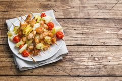 Kebab chicken, zucchini and tomatoes on skewers in a plate. Wooden table. Copy space.  royalty free stock photos