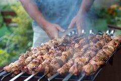 Kebab close up. Man cooking kebab, meat grilling on metal skewer, close up Royalty Free Stock Photos
