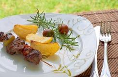 Kebab com batatas e tomates de cereja Imagens de Stock
