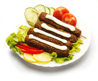 Kebab decorated with tomato, cucumber, and paprika Stock Images