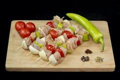 Kebab del pollo con il pomodoro, la cipolla ed i peperoni verdi su legno immagine stock