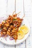Kebab del pollo con un limone e una cipolla su un fondo di legno Fotografia Stock