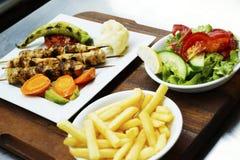 Kebab del pollo en una placa blanca con las verduras Foto de archivo libre de regalías