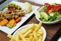 Kebab del pollo en una placa blanca con las verduras Fotos de archivo libres de regalías