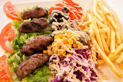 Kebab. Delicious kebab with a side dish of vegetables and potatoes fries stock photography