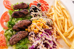 Kebab. Delicious kebab with a side dish of vegetables and potatoes fries stock image