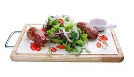 Kebab dell'agnello con insalata mista su un bordo di legno fotografie stock libere da diritti