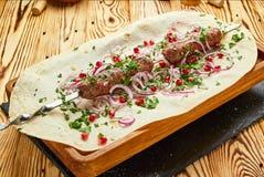 Kebab di Lula, piatto georgiano con carne servita dalle cipolle e verdi in pane della pita fotografie stock libere da diritti
