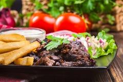 Kebab di manzo con le patate fritte e l'insalata Immagini Stock Libere da Diritti