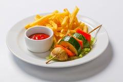Kebab di verdure spiedi arrostiti delle verdure sul piatto con le patate fritte Fotografia Stock