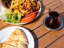 Kebab Doner на плите с французскими картофелем фри, томатами, луком и салатом Зажаренное мясо цыпленка и овечки с овощами и питой стоковые фотографии rf