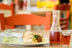 Kebab en pan Pita y verduras Grafin y dos vidrios de vino En la taberna en Grecia Imágenes de archivo libres de regalías