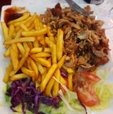 Kebab and fries. Plate of Kebab with French fries,  lettuce,  tomatoes,  red cabbage Royalty Free Stock Images