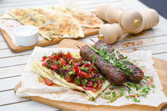 Kebab and Gozleme .Traditional oriental meat kebab of minced beef or lamb with vegetables and herbs overhead marble cutting boar. Gozleme with herb and cheese Royalty Free Stock Photo