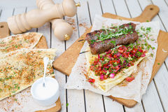 Kebab and Gozleme .Traditional oriental meat kebab of minced beef or lamb with vegetables and herbs overhead marble cutting boar. Royalty Free Stock Photos