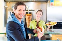 Kebab - Kunde und heißes Doner mit frischen Bestandteilen Lizenzfreies Stockbild