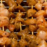 Kebab marinade chicken meat pepper flavored appetizing bright pieces close-up strung on wooden skewers against grill background stock image