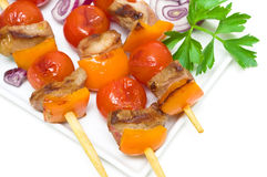 Kebab with meat and vegetables on a white plate on a white backg Stock Images
