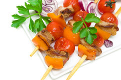 Kebab meat with vegetables on a white plate - white background. Stock Photos