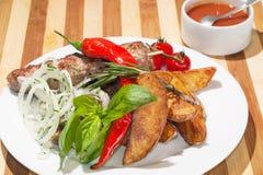 Kebab med bakade potatisar, körsbärsröda tomater och örter royaltyfria bilder