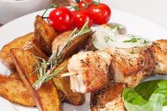 Kebab med bakade potatisar, körsbärsröda tomater och örter Arkivbilder