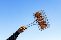 Kebab på gallret, i handen mot himlen fotografering för bildbyråer