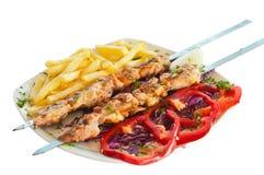 Kebab på steknålar med chiper arkivbild