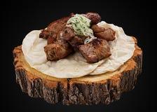Kebab of pork tenderloin on a wooden slice stock photos
