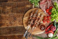 Kebab presentati su un bordo di legno Carne appetitosa cucinata su un fuoco aperto Natura morta con carne e gli ortaggi freschi immagini stock libere da diritti