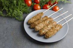 Kebab saporito del lule cucinato sugli spiedi di legno e servito sul piatto Verdure ed erbe come fondo immagine stock