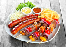 Kebab, Sausage and Fries on Plate with Sauces Stock Image