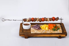 Kebab skewers of meat on a stick board Royalty Free Stock Photos