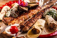 Kebab on skewers on a wooden tray with cherry tomatoes and hot pepper.  stock photography