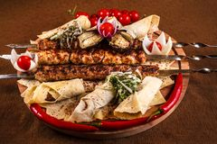 Kebab on skewers on a wooden tray with cherry tomatoes and hot pepper.  royalty free stock photo
