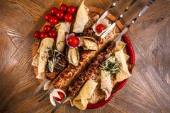 Kebab on skewers on a wooden tray with cherry tomatoes and hot pepper.  stock images