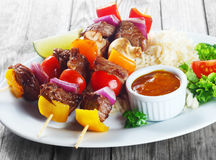 Kebab on Sticks with Sauce on Plate with Rice Royalty Free Stock Photo