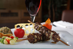 Kebab tomato and red wine. Kebab on a white dish with a glass of wine and vegetables Stock Images