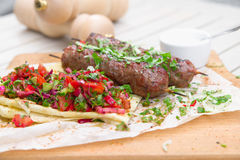 Kebab .Traditional oriental meat kebab of minced beef or lamb with vegetables and herbs overhead marble cutting boar. Royalty Free Stock Images