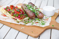 Kebab .Traditional oriental meat kebab of minced beef or lamb with vegetables and herbs overhead marble cutting boar. Royalty Free Stock Photos
