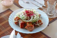 Kebab turco tradizionale sul piatto La carne arrostita e la cipolla sulla cima e mettono in salamoia Fotografia Stock