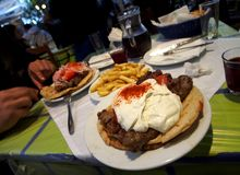 Kebab under Greek yoghurt on a pita - delicious food in a Greek tavern on a warm evening in Athens, Greece stock photography