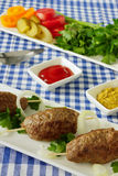 Kebab with vegetables and herbs. Three kebab on a white plate. The dish with vegetables and greens, ketchup and mustard Stock Photo