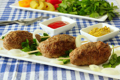 Kebab with vegetables and herbs. Three kebab on a white plate. The dish with vegetables and greens, ketchup and mustard Stock Image