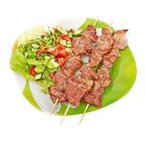 Kebab y ensalada en una placa verde Fotografía de archivo