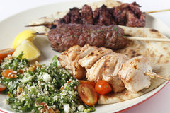 Kebab bbq meal closeup. Various barbecued kebabs - kofta, chicken tawook and sumac chicken - with tabouleh and pitta bread; an Arab or Lebanese-style feast Stock Photography