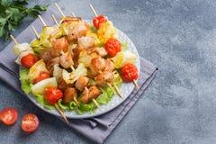 Kebabhöna, zucchini och tomater på steknålar i en platta Mörkt tabellkopieringsutrymme royaltyfri foto