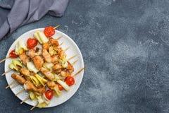 Kebabhöna, zucchini och tomater på steknålar i en platta Mörkt tabellkopieringsutrymme royaltyfria foton