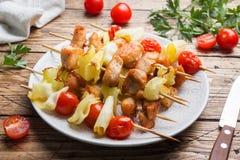 Kebabhöna, zucchini och tomater på steknålar i en platta table trä royaltyfria bilder