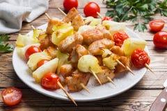 Kebabhöna, zucchini och tomater på steknålar i en platta table trä fotografering för bildbyråer